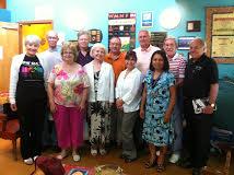 At May Field Trip to WMNF Community Radio in Tampa are, front l-r, Doris Norrito, LInda Valentino, Deborah Black, Sara Im; back, l-r, Keith Long, Randy Souutherland, Rick Rhodes, host Rob Lorei, Steve Traiman, Bob Ieva.